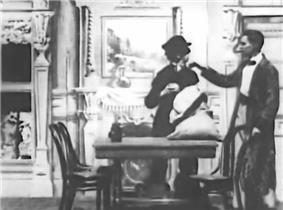 A frame of the black-and-white film. Sherlock Holmes enters his parlour and taps the shoulder of a burglar who is collecting Holmes' tablewares into a sack. Holmes is wearing a dressing gown and smoking a cigar, the thief is dressed in black.