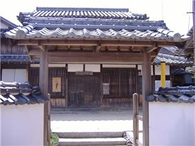 A roofed gate and a wooden house with white walls.