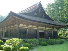 Wooden building with a hip-and-gable roof and an enclosing veranda.