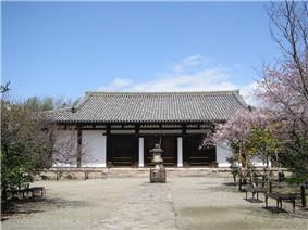 Low and wide wooden building with white walls.