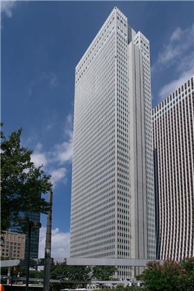 Ground-level view of a white, rectangular, window-dotted high-rise; one side is vertically bisected