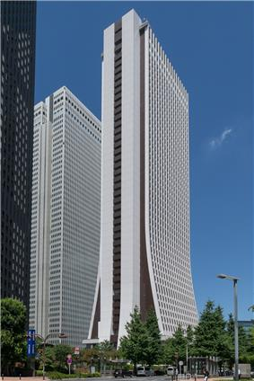 Ground-level view of a thin, brown and white high-rise; the two wider sides curve and flair out as they near the bottom