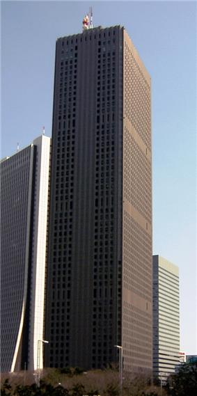 Ground-level view of a brown, rectangular high-rise; the window placement creates several horizontal bands on one side and one vertical stripe on the other