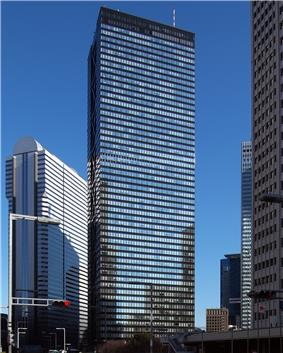 Ground-level view of a black, rectangular high-rise. its glass facades are highly reflective and the smaller facade is bisected by black, inset, crisscrossed beams
