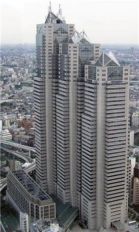 Aerial view of a beige high-rise lined with rows of windows; the building is composed of three adjoined towers of differing heights