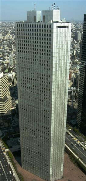 Aerial view of a gray, triangular, window-dotted high-rise