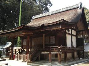 Wooden building with an asymmetric gabled roof and a raised veranda with handrail.