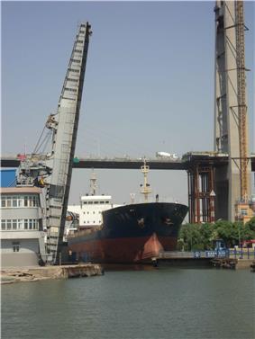 a ship exiting a canal through a raised drawbridge