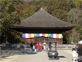 A wooden building with pyramid shaped roof. Colorful flags are hanging around the outer walls.