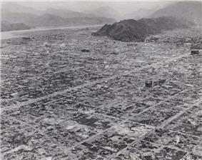 Black and white photo of a destroyed urban area. The outline of a grid pattern of streets is visible, but most buildings have been reduced to rubble.