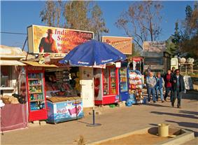 Two small shops offering Coca-Cola products and other soft drinks in glass-fronted refrigerated containers. In the middle is an umbrella with the Pepsi logo. Above them are aigns referencing Indiana Jones and depicting him. A small group of people is walking past and in front of them on the right