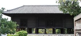 Dark wooden building with raised floor on poles.