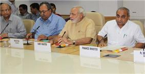 Modi flanked by three other men at a table
