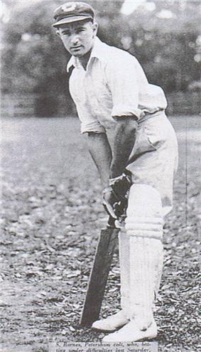 A teenage boy leans over his bat, in front of the stumps, in readiness to face a ball. He is wearing a white shirt, trousers and a cap