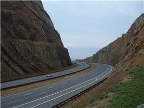 A highway passes through a cut through a mountain. The rock walls of the cut are visible above the highway.