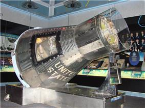 A conical, metallic-grey spacecraft, with a hole cut in one side to allow access, on a display stand inside a museum. It is covered in a close-fitting transparent plastic sheath.