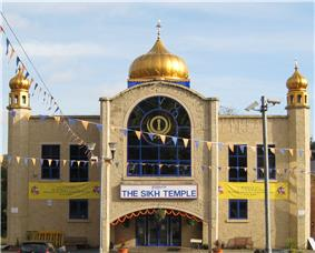 A large symmetrical two-storey building of yellow brick. The centre bay, incorporating the entrance, juts out. It has a large window with a semicircular top on the first floor and above is a golden onion dome on a blue base. At the ends of the frontage are hexagonal pilasters with small octagonal windowed pavilions and onion domes on top. Above the entrance is a white sign saying