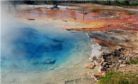 Blue spring with steam rising from it; irregular blotches of red and orange residue are on the banks, along with dead tree trunks.