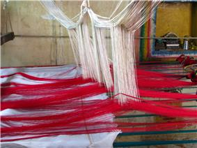 weaving with threads hanging from a loom