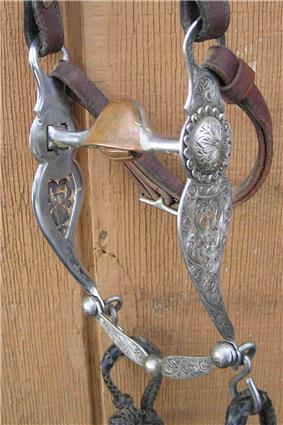 a horse bit with engraved silver shanks and a metal bar mouthpiece that is arched in the center with a copper hood over the arch