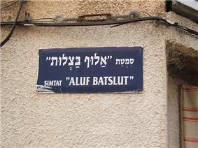 Hebrew street sign, above in Hebrew alphabet, below in Latin letter transliteration. Aluf Batslut veAluf Shum(he) (
