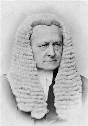 A man in a dated photograph in a suit with a white court wig.  His expression does not portray an emotion.