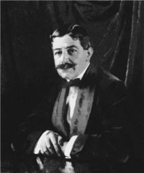 A Dark-haired gentleman with a bushy moustache leans, arms crossed on a table. He is wearing a velvet smoking jacket and bow-tie. A dark curtain is behind him.