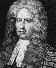 A middle-aged, slightly overweight man. He has long, curled hair, possibly a wig, and a heavy, decorated robe.