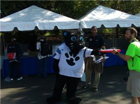 An anthropomorphic black cat, wearing a loose football jersey, is standing in front of several tents and is handing an object to another person.