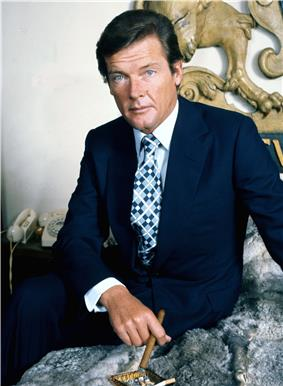 Roger Moore sits facing the camera in a relaxed pose, a cigar held in his right hand.