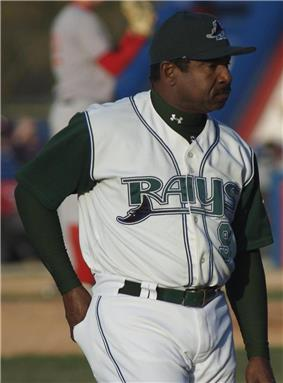 A man wearing a white baseball uniform with