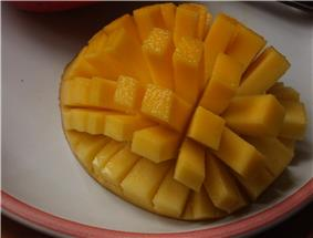 A halved, inside-out mango is cut in a grid pattern, still attached to the peel. The mango is inside-out, causing the resulting rectangles of fruit to splay out.