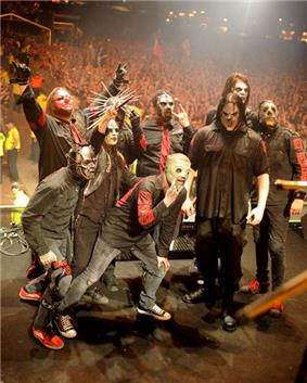Several members of Slipknot performing on stage, spotlit