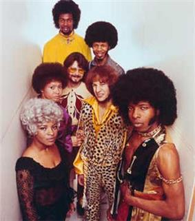 Seven young adults in garish clothes and hair. The most prominent is a black man in a vest with chains; he wears a large afro with sideburns, and looks with narrowed eyes and closed mouth at the camera. A black woman is in a platinum blonde wig and black dress. A white man with red hair wears a leopard print shirt and pants. There are two other black men, also in afros, another white man, with a short beard and glasses, and another black woman.