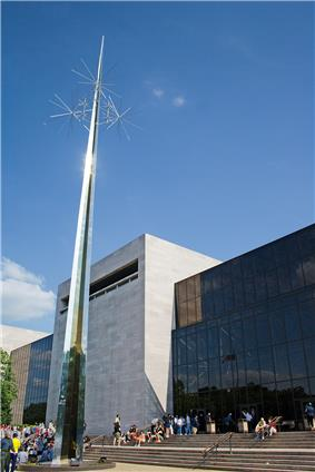 An angled view of a 3 story glass building, bisected by a wide, blank stone wall. There is a slender steel sculpture on the left.