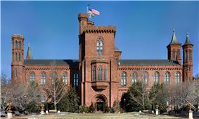 A brick building, reminiscent of a castle, slightly obscured by bare trees. There is a large central tower with the entrance at its base as well as smaller tower at each corner of the building, each with a varying design.