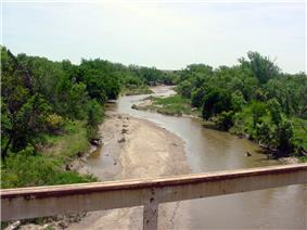 A small, muddy river, as seen from a bridge, meanders between tree-lined banks.