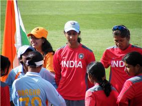 Eight female cricketers stand on a field. Two players are in red practice jerseys; three other players in red jerseys are facing toward them; a player in a blue shirt is facing away and hides another player in a blue game shirt. In the upper left corner is a fan with an Indian flag.