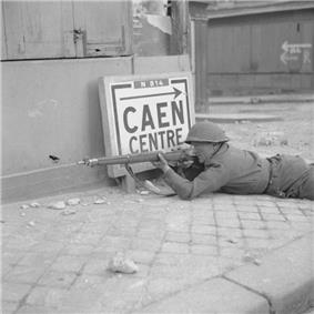 A soldier lies prone, rife at the ready by a building in a city street. Beside him is a sign reading