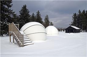 Two white observatory domes in a snow-covered field, wooden stairs are beside one dome and a cabin and trees are in the background