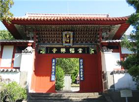 Small wooden gate painted in red, green and blue. Boards with Chinese characters are attached to the gate.