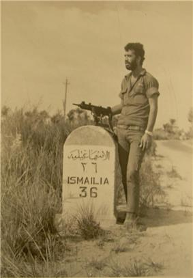 A soldier with an Uzi next to a road sign reading
