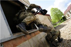 British soldier jumping out of a window on exercise