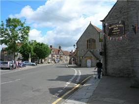 Street scene with houses and pub on the right and trees on the left.