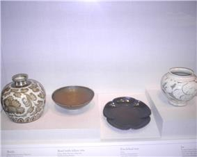 From left to right, a white, nearly spherical jar with a small top and a brown floral pattern glazed onto it, a shallow, unadorned, brown bowl, an unadorned black plate in the shape of a five petaled flower, and a white jar with a large opening and a grey vine pattern glazed into it.