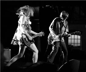 A woman and a man playing guitar in performance. The woman on the left is dressed in a short dress and the man on the right is in jeans and a shirt.