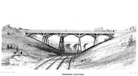A trestle bridge on four piers spans a cutting over two rail tracks