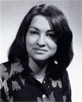 A formal pose of a young woman in her early twenties, dark straight hair parted near the center, wearing a dark floral print top.