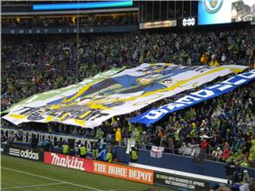 Fans in a stadium display a large banner. In the center is a picture of Thor wearing a green jersey and smashing the Union logo. It reads