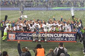 Several players are standing together with three trophies on the ground in front of them